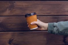 Free It`s Coffee Time! Woman`s Hand Holding Paper Cup Of Fresh Coffee Against Dark Wooden Background Taleawat Take Away Takeout Paper Royalty Free Stock Photo - 123581595