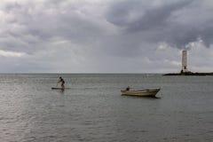 Itacaré Brasilien Augusti 19, 2018 En ung man står på havet under en molnig dag Ett litet fartyg som ankras på kusten och royaltyfria foton