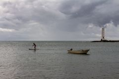 Itacaré, el Brasil 19 de agosto de 2018 Un hombre joven se coloca en el mar durante un día nublado Un bote pequeño anclado en la fotos de archivo libres de regalías