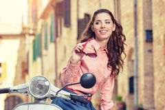 Itaian female sitting on scooter at old town's street. Stock Photo