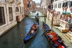 ITALIË, VENETIË - JULI 2012: Gondels met toeristen die een klein Venetiaans kanaal op 16 Juli, 2012 in Venetië kruisen. De gondel  Stock Fotografie