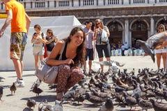 ITALIË, VENETIË - JULI 2012: Vrouw met duiven op beroemdste vierkant 16 Juli, 2012 in Venetië. Meer dan 20 miljoen toeristen komen Royalty-vrije Stock Foto's