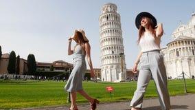 Itali?, Pisa Twee jonge vrouwen die in panamas op een achtergrond van de Leunende Toren van Pisa op een heldere dag lopen stock video
