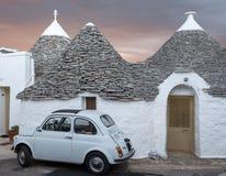 Italia Casa lavada blanca tradicional del trulli con blanco el cinquecento 500 del vintage de Fiat aparcamiento en frente, en Alb fotografía de archivo