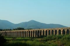 Italia En bro och ett berg Landskap arkivbild
