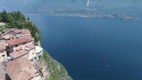 Italia Iglesia en la montaña y la ciudad vieja Panorama del lago magnífico Garda rodeado por las montañas vídeo almacen de video
