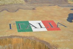 Italia with Italian Flag. Italia embossed on a stone monument, located in the heart of the Mediterranean Sea, Italy shares open land borders with France Royalty Free Stock Images