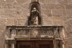 Italia, la isla de Cerdeña La ciudad de Alghero Una iglesia antigua en la ciudad medieval vieja Un anillo tallado a una puerta imagen de archivo