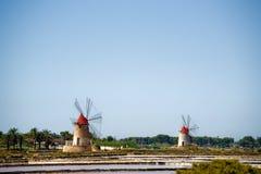 Italia Sicilia dos molinoes de viento viejos acerca al lago de sal Fotos de archivo