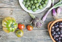 Italia, Toscana, Magliano, aceitunas en cuenco, cebollas de la primavera, tomates y alcachofa en la tabla de madera Fotografía de archivo libre de regalías