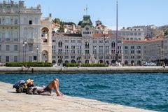 Italia, Trieste, turista que miente en el sol en el embarcadero atrevido foto de archivo
