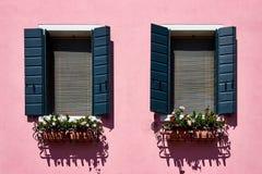 Italia, Venecia, isla de Burano Paredes y ventanas coloridas tradicionales con los obturadores verdes de las casas viejas Fotografía de archivo libre de regalías