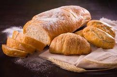 Italiaans brood en ander gebakken voedsel in houten lijst royalty-vrije stock afbeeldingen