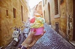 Italiaans die ijshoorntje ter beschikking op de achtergrond van op uitstekende straatatmosfeer wordt gehouden stock afbeelding
