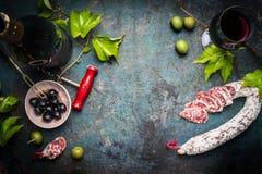 Italiaans stilleven met salami, rode wijn, olijven en druivenbladeren op donkere rustieke achtergrond, hoogste mening royalty-vrije stock afbeeldingen