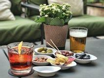Italiaanse antipasto met glazen van Americano en bier stock foto