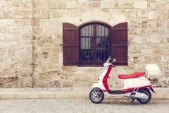 Italiaanse autopedvespa voor de muur met het venster royalty-vrije stock afbeelding