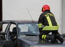 Italiaanse brandweerman terwijl onderbrekingen de glaswindscherm gebroken auto royalty-vrije stock afbeeldingen