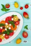 Italiaanse caprese salade met mozarellakaas, tomaten en basilicum op uitstekende houten achtergrond Hoogste mening, de ruimte van Stock Foto