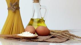 Italiaanse deegwaren, Italiaanse deegwareningrediënten, bloem, deegwarenassortiment van olijfolie in een fles, stilleven, kruiden stock footage
