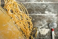 Italiaanse deegwaren, of noedels Vlak-leg met bloem, een mes voor knipsel De capaciteit om als culinaire achtergrond, boeken van  royalty-vrije stock afbeelding