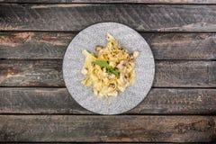 Italiaanse deegwarenfettuccine met kaas, kip en paddestoelen, diende op de mooie ceramische plaat royalty-vrije stock afbeelding