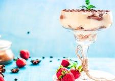 Italiaanse desserttiramisu in een glas op een blauwe achtergrond stock foto