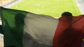 Italiaanse familie met kind die nationale vlag golven, die voor de sport van het voetbalteam toejuichen stock footage