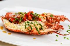 Italiaanse keuken Gehele die zeekreeft in half Gediend met tomatensalade en saus wordt gebakken en wordt gesneden op witte plaat royalty-vrije stock foto's
