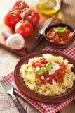 Italiaanse klassieke deegwarenfusilli met tomatensaus en basilicum Stock Foto