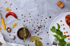 Italiaanse Kruiden Kom zwarte peper, Spaanse pepers en rozemarijn Salade naast een boonmaaltijd op een lijstachtergrond De ruimte stock afbeelding