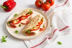 Italiaanse piadinaromagnola flatbread met Spaanse peper, tomaten, prosciuttoham, kaas en basilicum op de plaat op witte houten stock afbeeldingen