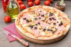 Italiaanse pizza met ham en olijven royalty-vrije stock foto