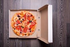 Italiaanse pizza met ham, tomaten, en olijven in doos Royalty-vrije Stock Foto