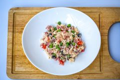 Italiaanse rijstsalade of koude rijst in een witte plaat op een hakbord met vage witte achtergrond royalty-vrije stock foto