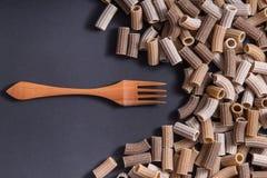 Italiaanse ruwe gekleurde gehele tarwedeegwaren met een houten vork Stock Afbeeldingen