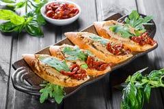 Italiaanse sandwiches - bruschetta met vleespastei, arugula, de in de zon gedroogde tomaat en de zaden op ciabatta paneren op don stock foto's