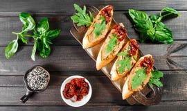 Italiaanse sandwiches - bruschetta met vleespastei, arugula, in de zon gedroogde tomaat en zaden op ciabattabrood stock foto