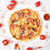Italiaanse smakelijke pizza met ingrediënten en kruiden op witte rustieke achtergrond Vlak leg, hoogste mening stock fotografie
