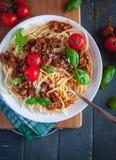 Italiaanse spaghetti met tomatensaus, Parmezaanse kaaskaas en vers basilicum op bovenkant, op donkere achtergrond, hoogste mening stock afbeelding