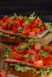 Italiaanse tomatenbruschetta met gehakte groenten, kruiden en olie op geroosterd of geroosterd knapperig ciabattabrood stock afbeelding