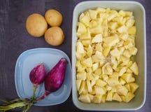 Italiaanse uien op blauwe plaat, aardappels en gesneden aardappelsmodel royalty-vrije stock afbeeldingen