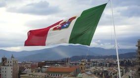 Italiaanse vlag die in de wind op de cityscape achtergrond fladderen voorraad Kleurrijke Europese vlag die voor hoogte golven stock videobeelden