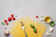 Italiaanse voedselachtergrond met ongekookte spaghetti, tomaat, basilicumbladeren, kaas, knoflook en olijfolie voor het koken op  stock afbeeldingen