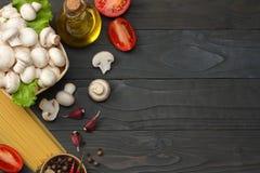 Italiaanse voedselachtergrond, met tomaten, peterselie, spaghetti, paddestoelen, olie, citroen, peperbollen op donkere houten lij Royalty-vrije Stock Afbeeldingen