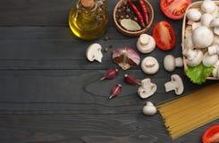 Italiaanse voedselachtergrond, met tomaten, peterselie, spaghetti, paddestoelen, olie, citroen, peperbollen op donkere houten lij Stock Afbeelding