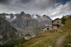 Italian Alps. Views of a mountain huts and mountains in the background in the Italian Alps Royalty Free Stock Photography