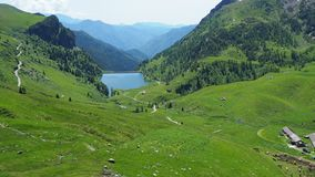 Italian Alps, Italy. Green meadows, pastures and artificial lake in spring time stock video footage