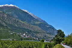 Italian Alps-view on the cyclist on the bicycle path to  and town  Ciardes Royalty Free Stock Images