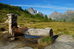 Italian Alps, water fountain. Water fountain made of wod, by a hiking trail. Italian Alps / Italian-Swiss border. Piemonte, Italy royalty free stock photos